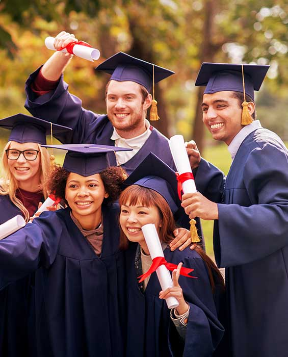 Students hold their diplomas, celebrating their graduation.