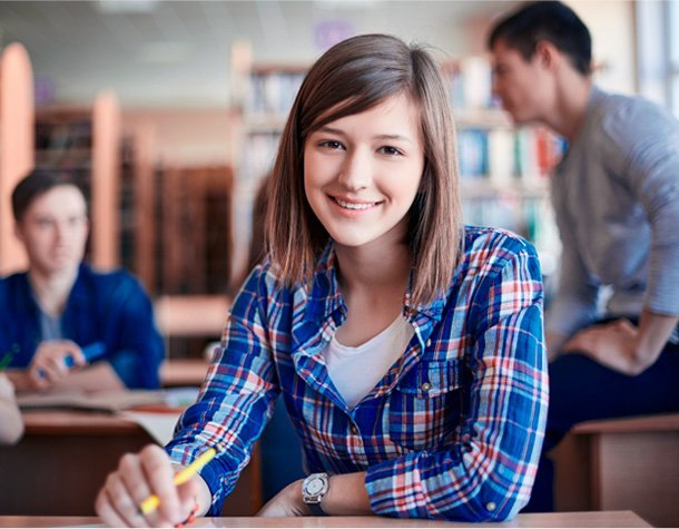 Student in classroom smiles with pen in hand while sitting at desk