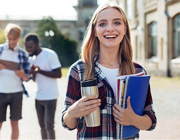 College student on campus with notebooks in hand