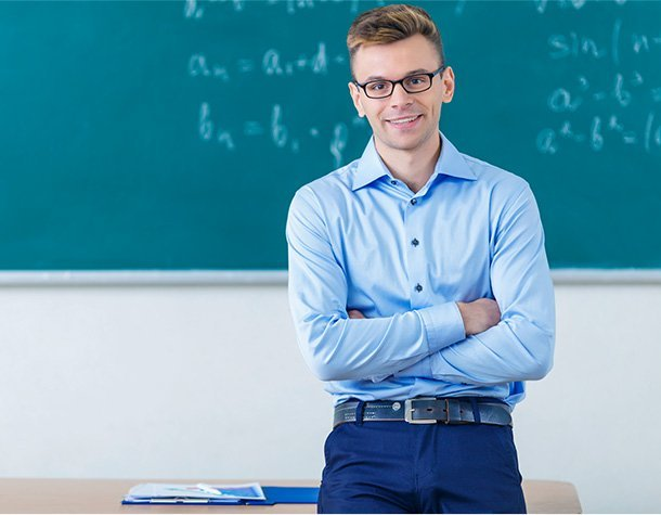 High school teacher stands at front of classroom with arms crossed